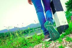 Fermez-vous vers le haut de la jambe de la femme prête à marcher sur la route Image libre de droits