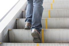 Fermez-vous vers le haut de la jambe des jeans de vêtements pour hommes, chaussures en cuir Position sur l'escalator Image libre de droits