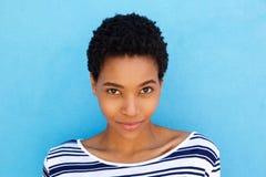 Fermez-vous vers le haut de la jeune femme africaine élégante sur le fond bleu photo libre de droits