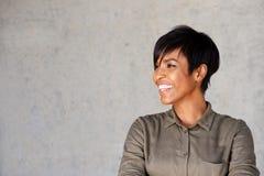 Fermez-vous vers le haut de la jeune femme africaine attirante semblant partie et du sourire Photo stock