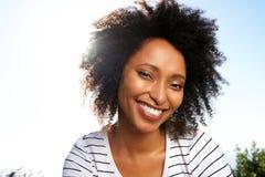 Fermez-vous vers le haut de la jeune femme africaine attirante souriant dehors contre le soleil lumineux photos stock