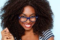 Fermez-vous vers le haut de la jeune femme d'afro-américain avec les verres de port de cheveux bouclés images libres de droits