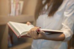 Fermez-vous vers le haut de la jeune femme lisant un livre à une bibliothèque Photos libres de droits