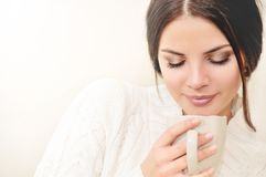 Fermez-vous vers le haut de la jeune femme réfléchie sentant l'arome d'un café d Photos stock