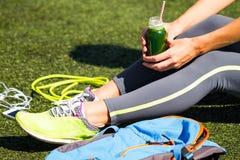 Fermez-vous vers le haut de la jeune femme sportive tenant le jus vert se reposant sur l'herbe Photos stock