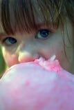 Fermez-vous vers le haut de la jeune fille mangeant la sucrerie de coton Photos libres de droits