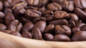 Fermez-vous vers le haut de la longueur de tourner les grains de café rôtis dans la cuvette en bois banque de vidéos