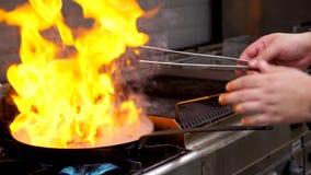 Fermez-vous vers le haut de la longueur du cuisinier faisant frire la viande de sein de canard avec la flamme nue banque de vidéos