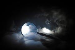 Fermez-vous vers le haut de la loupe simple avec la poignée noire, se penchant sur le Tableau en bois sur le fond d'obscurité de  Photos stock