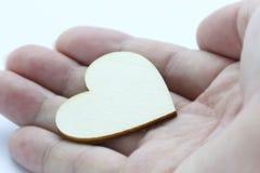 Fermez-vous vers le haut de la macro main d'homme tenant le coeur en bois, symbole d'amour sur le fond blanc Image libre de droits