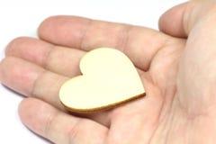 Fermez-vous vers le haut de la macro main d'homme tenant le coeur en bois, symbole d'amour sur le fond blanc avec le foyer sélect Photo libre de droits