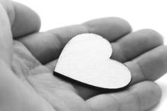 Fermez-vous vers le haut de la macro main d'homme tenant le coeur en bois, symbole d'amour sur le fond blanc, effet noir et blanc Photos stock