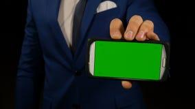 Fermez-vous vers le haut de la main de l'homme d'affaires tenant le téléphone intelligent avec l'écran vert banque de vidéos