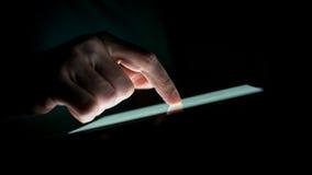 Fermez-vous vers le haut de la main de l'homme touchant un dispositif d'écran tactile Photo libre de droits