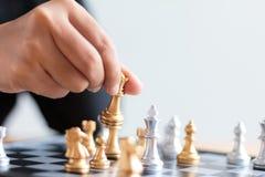 Fermez-vous vers le haut de la main de tir des échecs d'or mobiles de femme d'affaires au defe Image stock