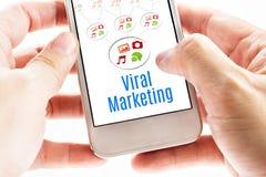Fermez-vous vers le haut de la main deux tenant le téléphone intelligent avec le mot viral de vente Photo stock