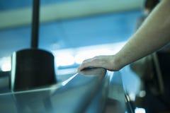 Fermez-vous vers le haut de la main du ` s de personne se relevant sur l'escalator photo libre de droits