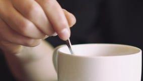 Fermez-vous vers le haut de la main femelle remuant la tasse de café lentement banque de vidéos