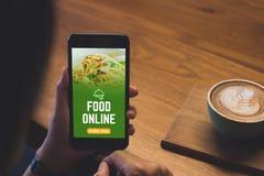 Fermez-vous vers le haut de la main de femme tenant les apps mobiles en ligne de nourriture avec le cof chaud image libre de droits