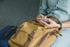 Fermez-vous vers le haut de la main de femme utilisant le téléphone portable avec le sac à dos et les suitcas images stock