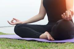 Fermez-vous vers le haut de la main La femme font le yoga extérieur Femme exerçant le yoga au fond de mer Concept de la vie saine Photo libre de droits