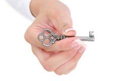 Fermez-vous vers le haut de la main Manicured retenant la clé squelettique Photos stock