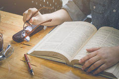 Fermez-vous vers le haut de la main tenant des lunettes avec la lecture, reposez un les yeux du ` s i Photo stock