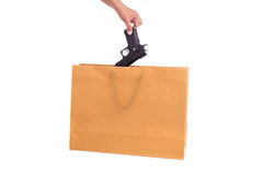 Fermez-vous vers le haut de la main tenant l'arme à feu dans le sac de papier brun d'isolement sur le blanc Photo libre de droits