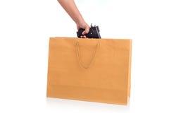 Fermez-vous vers le haut de la main tenant l'arme à feu dans le sac de papier brun d'isolement sur le blanc Photos stock