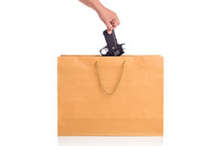 Fermez-vous vers le haut de la main tenant l'arme à feu dans le sac de papier brun d'isolement sur le blanc Image libre de droits
