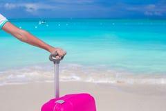 Fermez-vous vers le haut de la main tenant la valise sur la plage tropicale Photos libres de droits