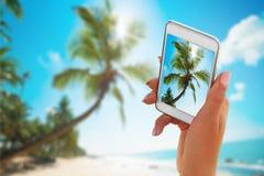 Fermez-vous vers le haut de la main tenant le smartphone sur la plage d'été technologie, voyage, tourisme, communication et conce Photographie stock
