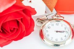 Fermez-vous vers le haut de la montre de poche et les roses rouges fleurissent Image stock