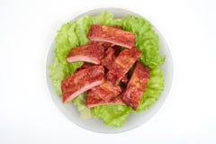 Fermez-vous vers le haut de la nervure de porc grillée du plat d'isolement sur le fond blanc photographie stock