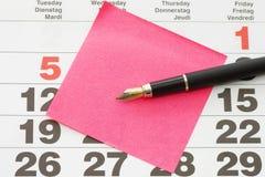 Fermez-vous vers le haut de la note de post-it sur le calendrier Images libres de droits
