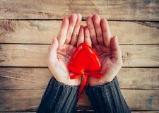 Fermez-vous vers le haut de la participation de femme de main et du coeur rouge de personne sur la table en bois Photo stock