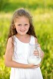 Fermez-vous vers le haut de la petite fille de portrait tenant le broc d'été extérieur de lait photos libres de droits