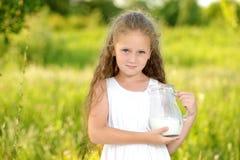 Fermez-vous vers le haut de la petite fille de portrait tenant le broc d'été extérieur de lait images libres de droits