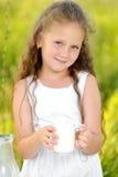 Fermez-vous vers le haut de la petite fille de portrait tenant le verre d'été extérieur de lait photo libre de droits
