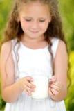 Fermez-vous vers le haut de la petite fille de portrait tenant le verre d'été extérieur de lait photographie stock libre de droits
