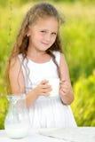 Fermez-vous vers le haut de la petite fille de portrait tenant le verre d'été extérieur de lait photo stock