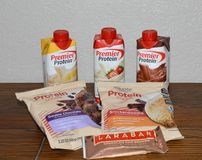 Fermez-vous vers le haut de la photo de 2 biscuits de protéine, de 1 barre de protéine et de 3 saveurs différentes des secousses  photos stock