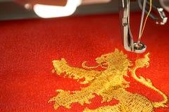 Fermez-vous vers le haut de la photo de la conception de lion de machine et d'or de broderie Photo stock