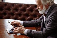 Fermez-vous vers le haut de la photo cultivée du vieil homme faisant l'achat en ligne Image stock