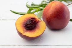Fermez-vous vers le haut de la photo d'un fruit mûr de nectarine et on a coupé en demi o Photos stock