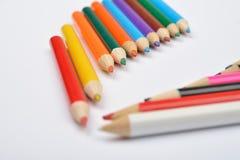Fermez-vous vers le haut de la photo de beaucoup de crayons colorés peu de crayon sur le blanc Photo libre de droits