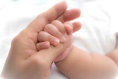 Fermez-vous vers le haut de la photo de la mère tenant la main de bébé Photo stock