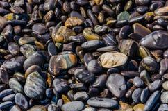 Fermez-vous vers le haut de la photo de la pierre brillante noire sur la plage de roche photographie stock libre de droits