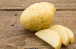 Fermez-vous vers le haut de la photo de la pomme de terre et des tranches fraîches entières sur la table en bois Images libres de droits