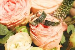 Fermez-vous vers le haut de la photo des anneaux de mariage sur la rose de rose Photos stock